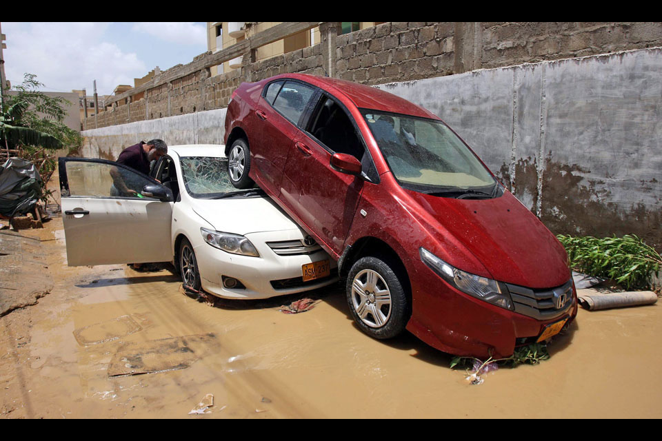 People check their damaged vehicles following torrential rains in Karachi