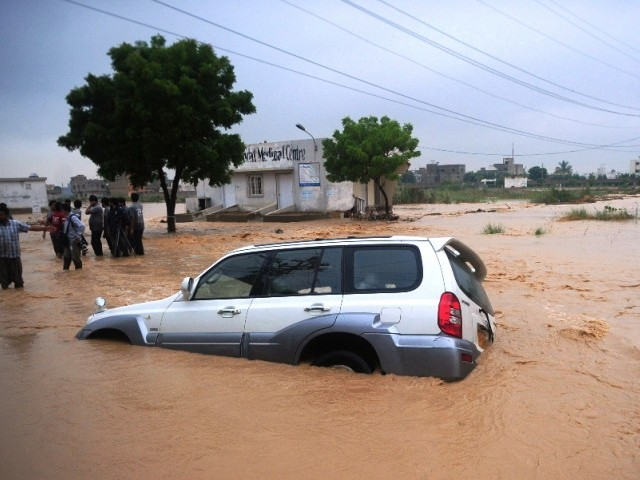 Residents stand near a partially submerged vehicle as they evacuate a flooded area in Karachi