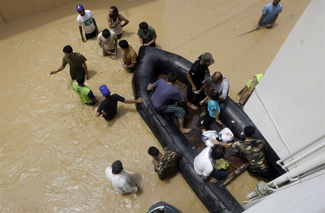 Pakistani soldiers rescue local residents from an area flooded by heavy rains on the outskirts of Karachi
