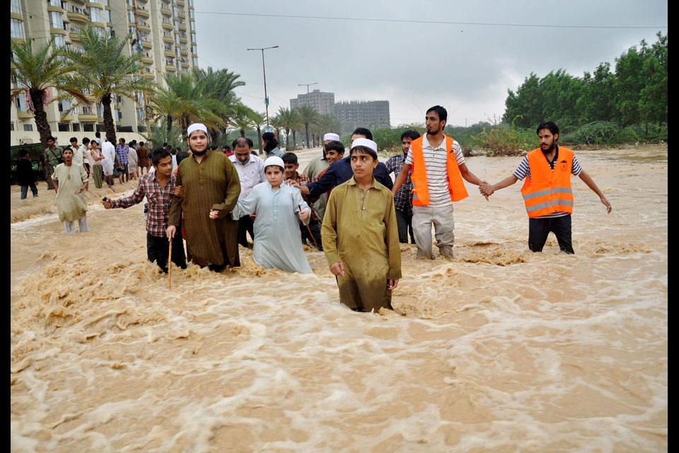 People evacuate flooded areas following heavy rains in Karachi