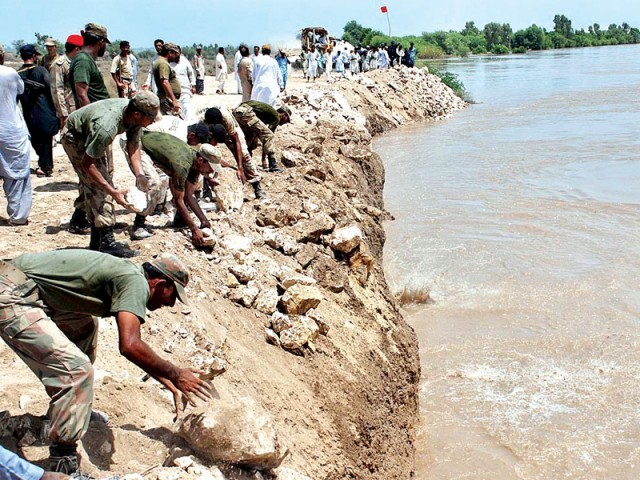Pakistan Army officials dump stones to strengthen the embankment along River Indus at Aqil Agani