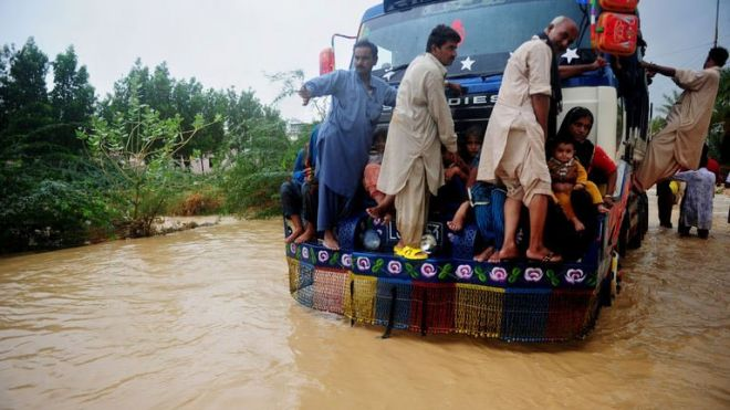 Pakistani residents ride on a truck as they evacuate a flooded area in Karachi