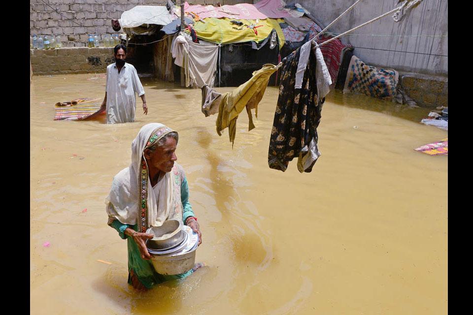 A woman wades through flood waters following a heavy monsoon in Karachi