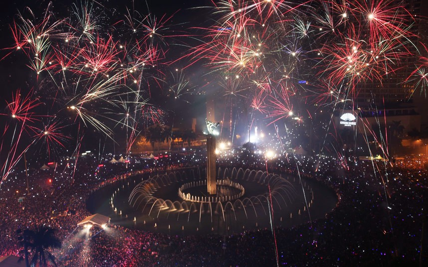 Fireworks explode as thousands of people gather to watch in the main business district on New Year