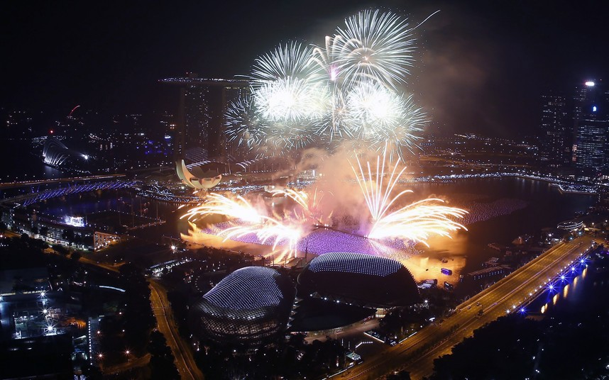 Fireworks go off in Singapore over the Marina Bay area with the iconic Esplanade theatre in the foreground