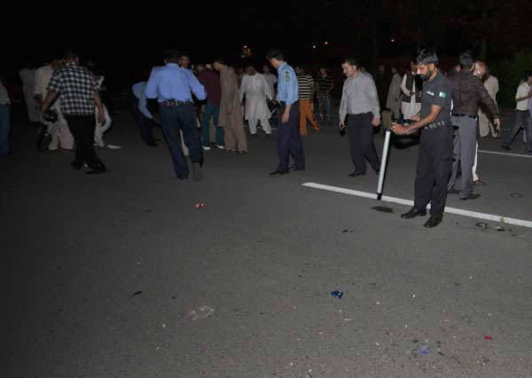 Bomb disposal staff and security officials collect evidence at the location where an unidentified gunman was shot and arrested by security officials in Islamabad August 15, 2013.