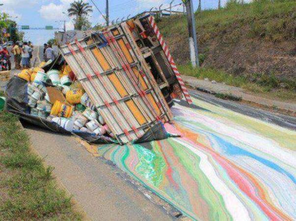 A truck carrying cans of paint tips over and creates a beautiful mess