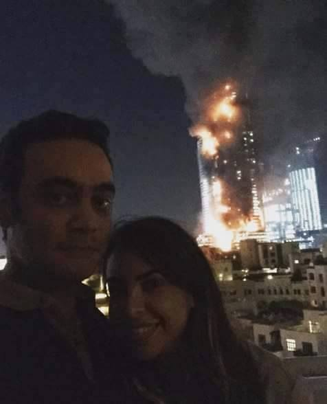 Couple clicks selfie with a burning Hotel  in the background