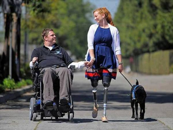 A man in a wheelchair, his wife with prosthetic legs & Dog